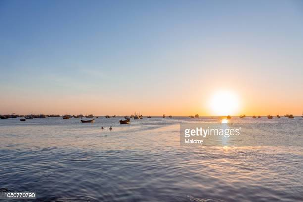 panoramic view at fisher boats floating on the water at sunset. mui ne, binh thuan, vietnam. - vietnam ストックフォトと画像