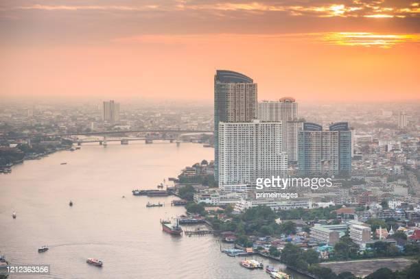 サパンタクシン、シーロム、サトーン川、チャオプラヤー川、バンコク、タイの街並みビジネス地区のパノラマビュー は、夕暮れ時の高い建物から - シーロム ストックフォトと画像