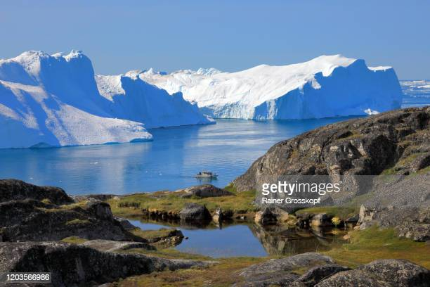 panoramic view from a rocky mountain at a small ship and huge icebergs in the icefjord - rainer grosskopf stockfoto's en -beelden