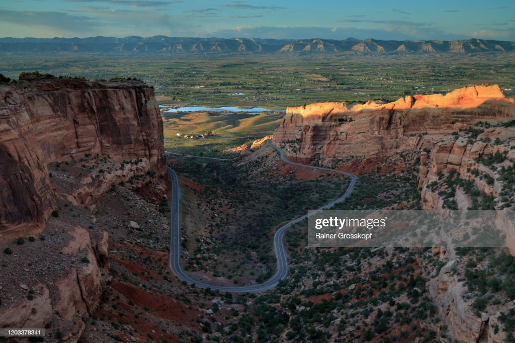 Panoramic view into a valley with a winding road at sunset : Stock Photo
