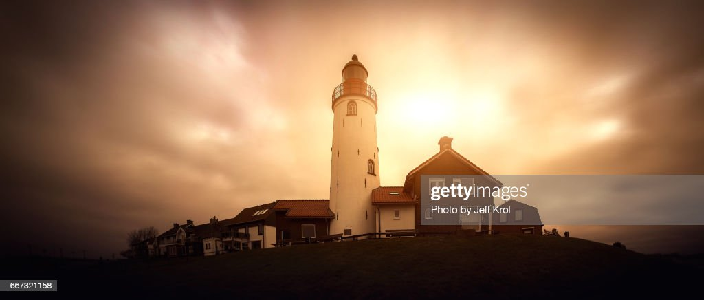Panoramic view of a lighthouse on a hill with houses, windy sky with sun coming through the clouds. : Stock Photo