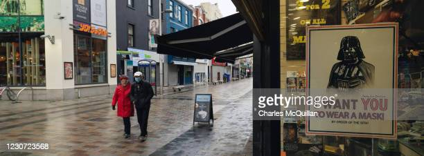 Panoramic view of a near deserted Belfast city centre as a shop window sign featuring Star Wars character Darth Vader advises passers by to wear a...