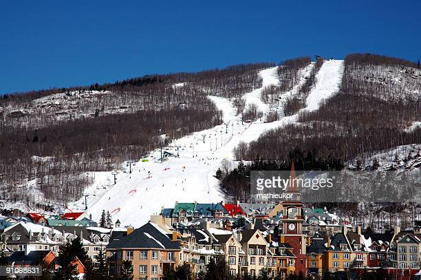 panoramic view of a ski hill with village below - mont tremblant stock pictures, royalty-free photos & images