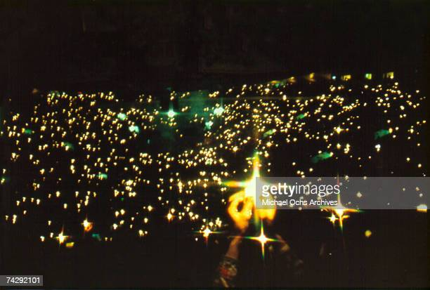 A panoramic view of a stadium rock concert taken from the back of the venue with the only showing light coming from the audience raising lighters...