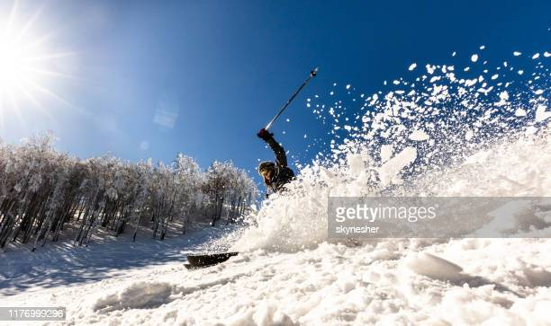 panoramic view of a woman splashing snow while skiing on a mountain. - downhill skiing stock pictures, royalty-free photos & images