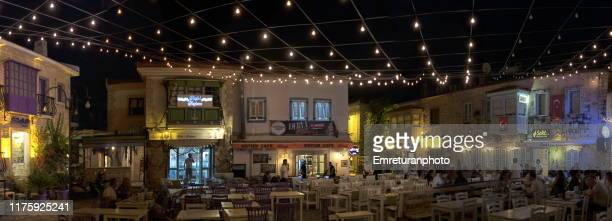 panoramic view of an illuminated square with people sitting at restaurants in alacati - emreturanphoto stock-fotos und bilder