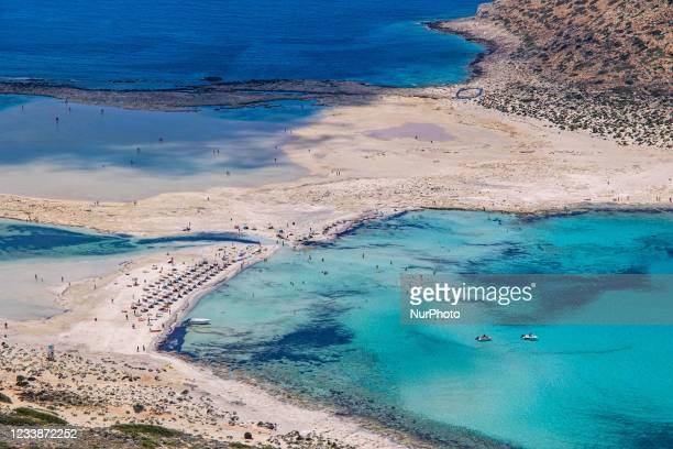 Panoramic view of Balos Beach with the umbrellas, sundecks and people swimming, the incredible lagoon with the turquoise exotic and tropical water of...