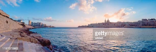 マルタの日の出のバレッタ、スリーマ、マノエル島の都市景観でカルメル山の聖母のパノラマビュー - バレッタ ストックフォトと画像