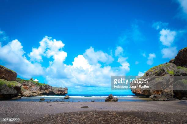 panoramic view of beach against sky - northern mariana islands stock pictures, royalty-free photos & images