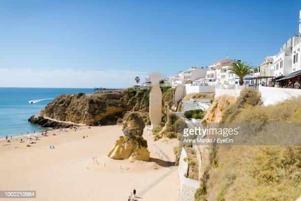 panoramic view of beach and buildings against sky - albufeira stock pictures, royalty-free photos & images