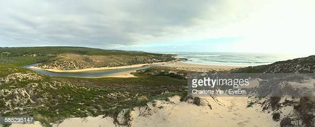 Panoramic View Of Beach And Sea Against Cloudy Sky