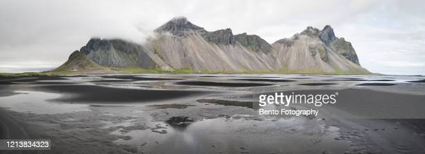 panoramic view of black lava beach, mount vestrahorn, stokksnes, eastern region, iceland - international landmark stock pictures, royalty-free photos & images