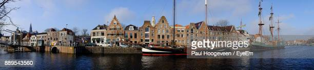 panoramic view of boats moored in river by buildings in city - haarlem stock photos and pictures
