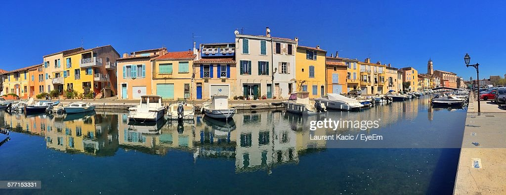 Panoramic View Of Boats Moored On Canal Against Buildings At Martigues : Stock Photo