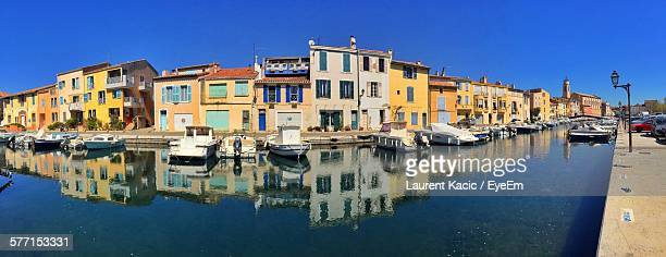 Panoramic View Of Boats Moored On Canal Against Buildings At Martigues