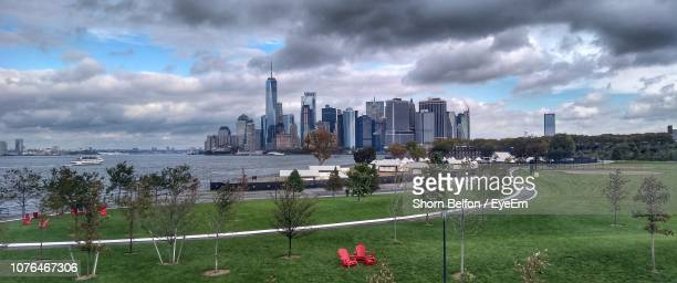 panoramic view of buildings against cloudy sky - governors island stock pictures, royalty-free photos & images