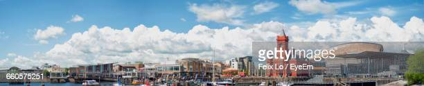 panoramic view of buildings and church by harbor against cloudy sky - cardiff stock pictures, royalty-free photos & images