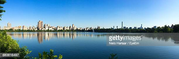 Panoramic View Of Buildings In City Against Clear Blue Sky Reflecting On Pond At Central Park