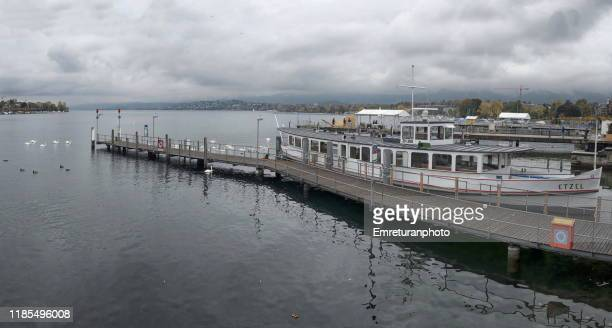 panoramic view of burkiplatz pier with anchored tour boats at zurich lake. - emreturanphoto stock pictures, royalty-free photos & images