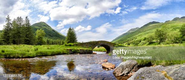 panoramic view of butter bridge over kinglas water in the loch lomond national park in scotland - hill stock pictures, royalty-free photos & images