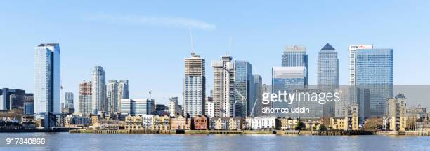 panoramic view of canary wharf and the city skyline across river thames - canary wharf stock photos and pictures
