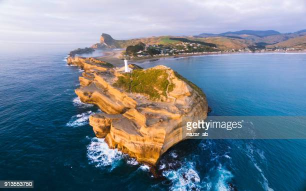 panoramic view of castlepoint lighthouse with castlepoint village in background during sunrise. - wellington new zealand stock photos and pictures