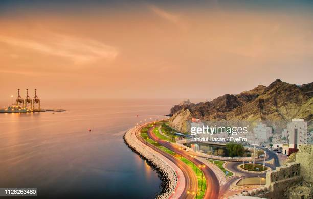 panoramic view of city by sea against sky during sunset - oman fotografías e imágenes de stock