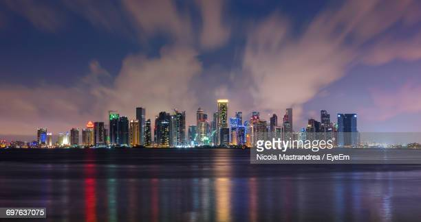 panoramic view of city lit up at night - doha stock photos and pictures