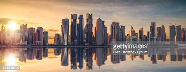 panoramic view of city skyline reflecting on bay during sunset - doha stock photos and pictures