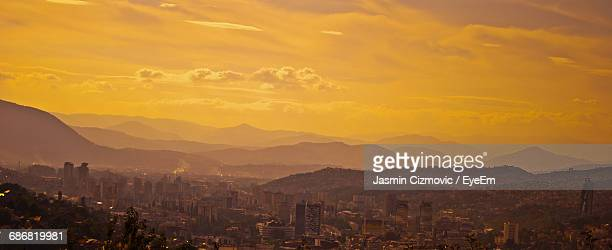 panoramic view of cityscape and mountains against orange sky - sarajevo stock-fotos und bilder