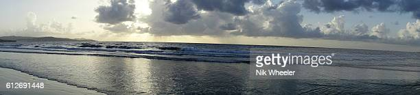 panoramic view of cloudy sky at dawn over beach on the atlantic ocean coast of tropical island of tobago in trinidad and tobago. - marina wheeler foto e immagini stock