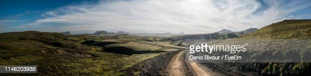 panoramic view of dirt road against sky - country road stock pictures, royalty-free photos & images