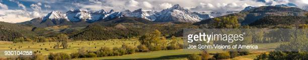 Panoramic view of Double RL Ranch owned by Ralph Lauren shows Hay Bales under Mount Sneffels and San Juan Mountains in Autumn outside Ridgway Colorado