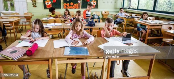 panoramablick von grundschülern im klassenzimmer. - kind im grundschulalter stock-fotos und bilder