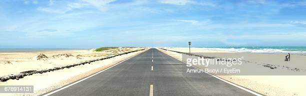 Panoramic View Of Empty Road By Beach Against Sky On Sunny Day