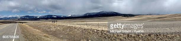 Panoramic View Of Empty Road By Landscape And Mountains Against Cloudy Sky
