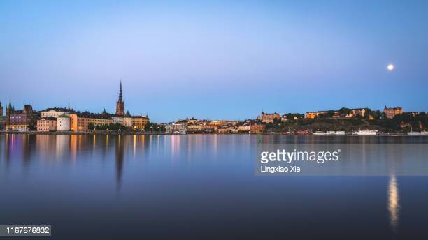 panoramic view of famous riddarholmen and riddarholm church with reflection at sunset with moon, stockholm, sweden - riddarholmkirche stock-fotos und bilder