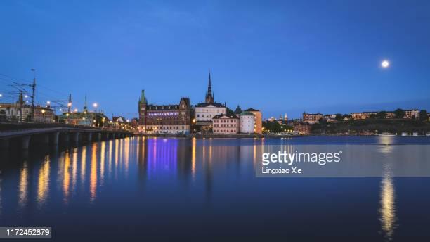panoramic view of famous riddarholmen, gamla stan reflected at dusk with moon, stockholm, sweden - riddarholmkirche stock-fotos und bilder