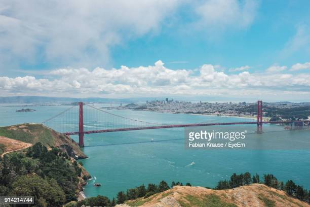 panoramic view of golden gate bridge over sea against cloudy sky - suspension bridge stock photos and pictures