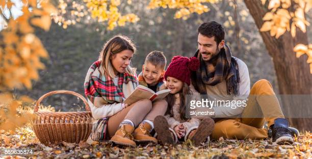 Panoramic view of happy family reading a book in autumn day on a picnic.