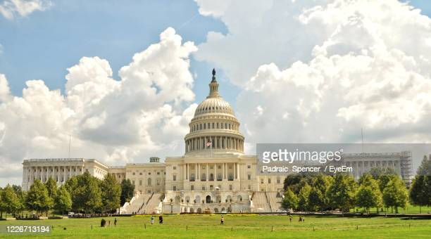 panoramic view of historical united states capitol congress building against sky - united states capitol rotunda stock pictures, royalty-free photos & images
