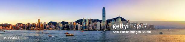 panoramic view of hong kong skyline at sunset - hong kong victoria harbour stock pictures, royalty-free photos & images
