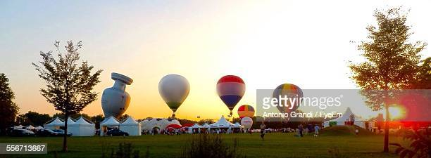 panoramic view of hot air balloons and people during ballooning festival - balloon fiesta stock pictures, royalty-free photos & images