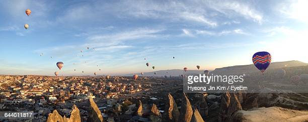 Panoramic View Of Hot Air Balloons Flying Over Cappadocia Against Sky