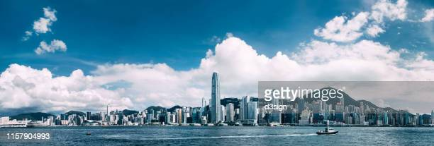 panoramic view of iconic hong kong city skyline with victoria harbour against clear blue sky - hong kong stock pictures, royalty-free photos & images