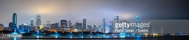 panoramic view of illuminated buildings against sky at night - florin seitan stock pictures, royalty-free photos & images