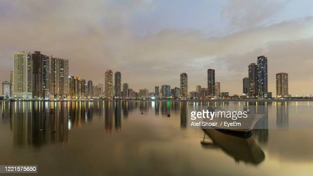 panoramic view of illuminated city by sea against sky - emirate of sharjah stock pictures, royalty-free photos & images