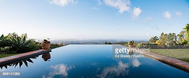 panoramic view of infinity pool against landscape - infinity pool foto e immagini stock
