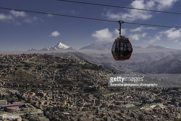 Panoramic view of La Paz, a red cable car (teleferico) and the snowcapped peaks of Huayna Potosi, Bolivia