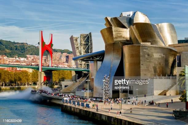 フランク・ゲーリー、ネルビオン川、ビルバオ、スペインによって設計されたラ・サルヴェ橋とグッゲンハイム美術館のパノラマビュー - 現代美術館 ストックフォトと画像